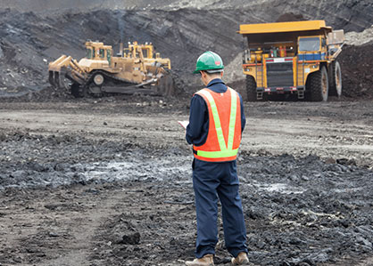 Accounting for mining companies shown by a worker and heavy duty equipment in an open pit mine.